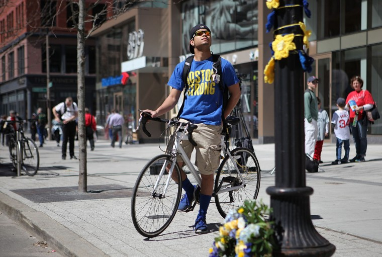 Melvin Morales, 20, of Rhode Island looks up at a memorial on Boylston Street commemorating the two-year anniversary of the 2013 Boston Marathon bombings on April 15, 2015 in Boston, Massachusetts. Two years ago, two pressure cooker bombs killed three and injured an estimated 264 others during the Boston marathon, on April 15, 2013. (Photo by Tim Bradbury/Getty Images)