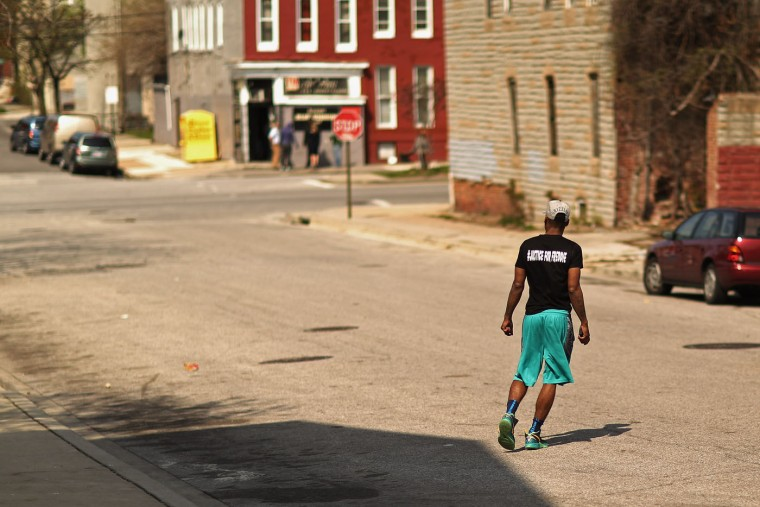 A young man wears a shirt with the message 'Justice For Freddie' in the Sandtown neighborhood where he lives April 21, 2015 in Baltimore, Maryland. Gray was a 25-year-old black man who lived in this neighborhood and was arrested for possessing a switch blade knife April 12 outside the Gilmor Homes housing project on Baltimore's west side. According to his attorney, Gray died a week later in the hospital from a severe spinal cord injury he received while in police custody. (Photo by Chip Somodevilla/Getty Images)