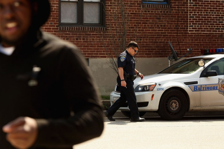 A police officer returns to his vehicle after responding to an emergency call at the Gilmor Homes in the Sandtown neighborhood April 21, 2015 in Baltimore, Maryland. Freddie Gray, a 25-year-old black man who lived in this neighborhood, was arrested for possessing a switch blade knife April 12 outside this housing project on Baltimore's west side. According to his attorney, Gray died a week later in the hospital from a severe spinal cord injury he received while in police custody. (Photo by Chip Somodevilla/Getty Images)
