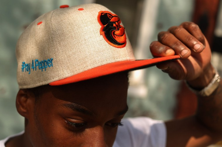 A young man who game his name only as 'Mike' shows support for Freddie Gray by wearing a hat embroidered with '#Pray4Pepper' in the Sandtown neighborhood where he lives April 21, 2015 in Baltimore, Maryland. Gray, whose nickname was Pepper, was a 25-year-old black man who lived in this neighborhood and was arrested for possessing a switch blade knife April 12 outside the Gilmor Homes housing project on Baltimore's west side. According to his attorney, Gray died a week later in the hospital from a severe spinal cord injury he received while in police custody. (Photo by Chip Somodevilla/Getty Images)