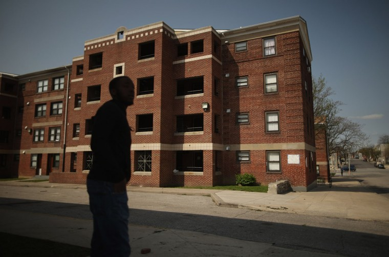 A young man stands outside the Gilmor Homes housing project building where Freddie Gray was arrested in the Sandtown neighborhood April 21, 2015 in Baltimore, Maryland. Gray, a 25-year-old black man who lived in the neighborhood, was arrested for possessing a switch blade knife April 12 outside this building on Baltimore's west side. According to his attorney, Gray died a week later in the hospital from a severe spinal cord injury he received while in police custody. (Photo by Chip Somodevilla/Getty Images)