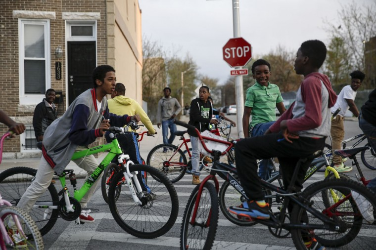 Children on bikes look on as protesters march march for Freddie Gray on Laurens Street, April 21, 2015 in Baltimore, Maryland. Gray, 25, died from spinal injuries on April 19, one week after being taken into police custody. (Photo by Drew Angerer/Getty Images)