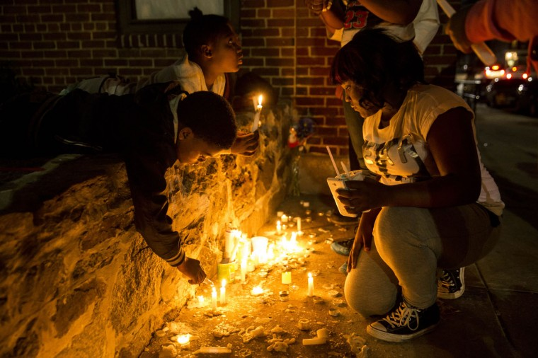 Neighborhood children light candles at a memorial after a march and vigil for Freddie Gray, April 21, 2015 in Baltimore, Maryland. Gray, 25, died from spinal injuries on April 19, one week after being taken into police custody. (Photo by Drew Angerer/Getty Images)