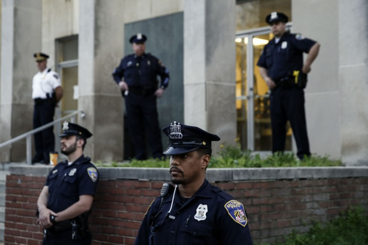 Baltimore Police officers look on during a rally for Freddie Gray in front of the Baltimore Police Department's Western District police station, April 21, 2015 in Baltimore, Maryland. Gray, 25, died from spinal injuries on April 19, one week after being taken into police custody. (Photo by Drew Angerer/Getty Images)