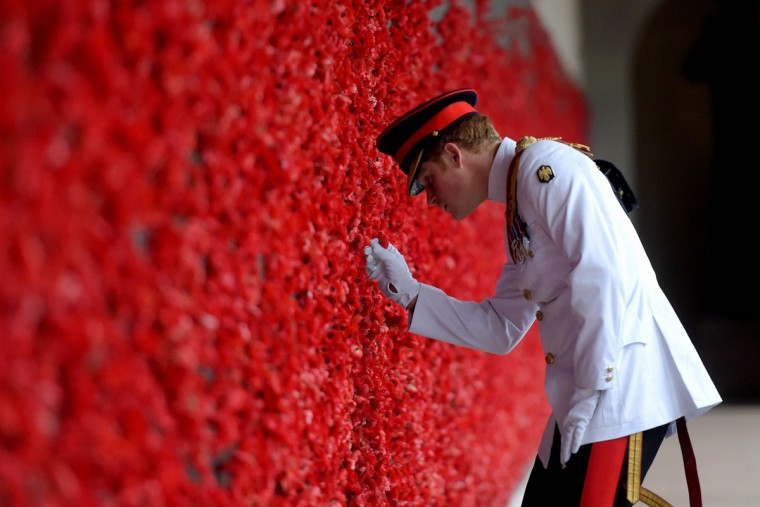 Britain's Prince Harry places a poppy at the Roll of Honour during a visit to the Australian War Memorial in Canberra on April 06, 2015. Harry arrived in Canberra ahead of a one-month attachment with the Australian Army, as he moves towards his retirement from the British military. (AFP Photo/Lukas Coch)