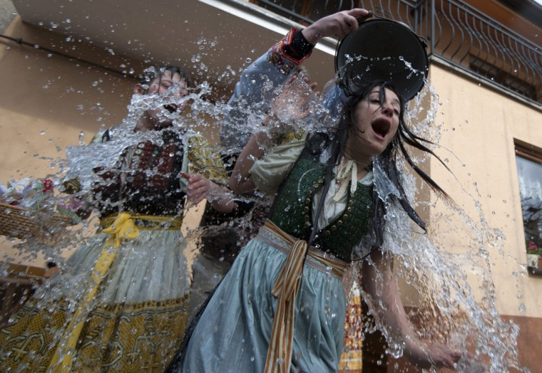 A young Slovak dressed in traditional costume (C) throws a bucket of water over a girl as part of Easter celebration in the village of Trencianska Tepla, north-western Slovakia, on April 6, 2015. Slovakia's men splash women with water and hit them with a willow to symbolize youth, strength and beauty for the upcoming spring season. (AFP Photo/Samuel Kubani)