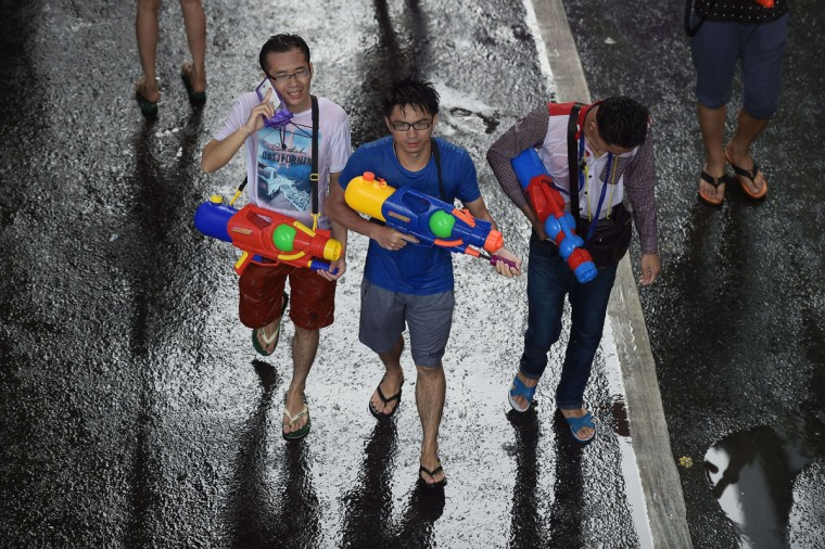 Revelers take part in water fights as they celebrate the Thai traditional New Year in a water festival known as Songkran, at Silom road in Bangkok on April 13, 2015. (AFP Photo/Christophe Archambault)