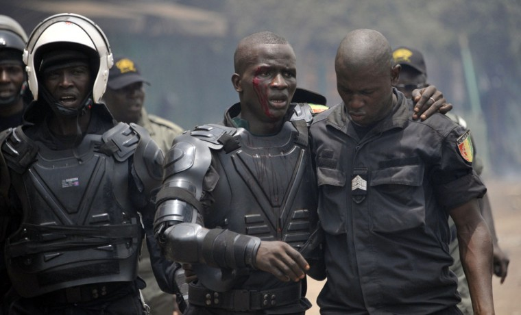 Blood runs down the face of an injured anti-riot police officer as he is assisted by a colleague during clashes with opposition protesters during a demonstration in Conakry on April 13, 2015. Several protesters were wounded on April 13 as Guinean police opened fire during violent demonstrations across the capital Conakry against the regime of President Alpha Conde. (AFP Photo/Cellou Binani)