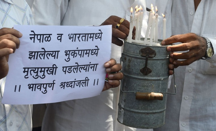 Indian Dabbawalas - Mumbai's famous army of lunchbox delivery men - light candles atop a lunchbox before the start of their daily round in Mumbai on April 27, 2015, in memory of the people killed in the devastating earthquake over the weekend in Nepal and India. Tens of thousands of frightened Nepalese huddled in tents desperate for help, two days after a quake killed more than 3,500 people, as international rescue teams with sniffer dogs raced to find survivors buried in the rubble. (AFP Photo/P /indranil )