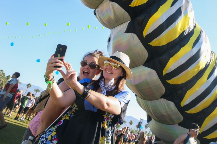 Festival goers pose in front of a caterpillar art installation at the 2015 Coachella Music and Arts Festival on Friday, April 17, 2015, in Indio, Calif. (Photo by Rich Fury/Invision/AP)