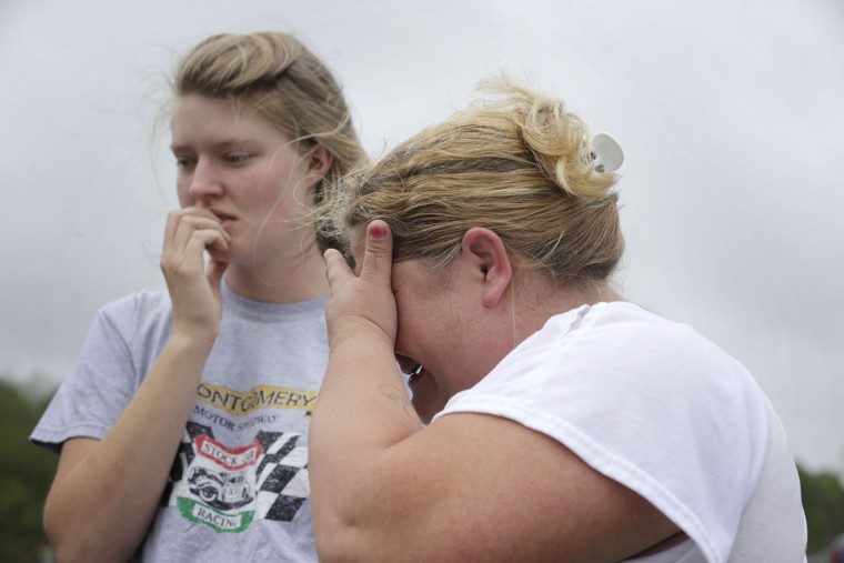 Kristie Brasher, right, cries next to a friend Monday, April 13, 2015, after a gunman entered a doctor's office, shot a woman and fled to a nearby home in Jemison, Ala. (AP Photo/Brynn Anderson)