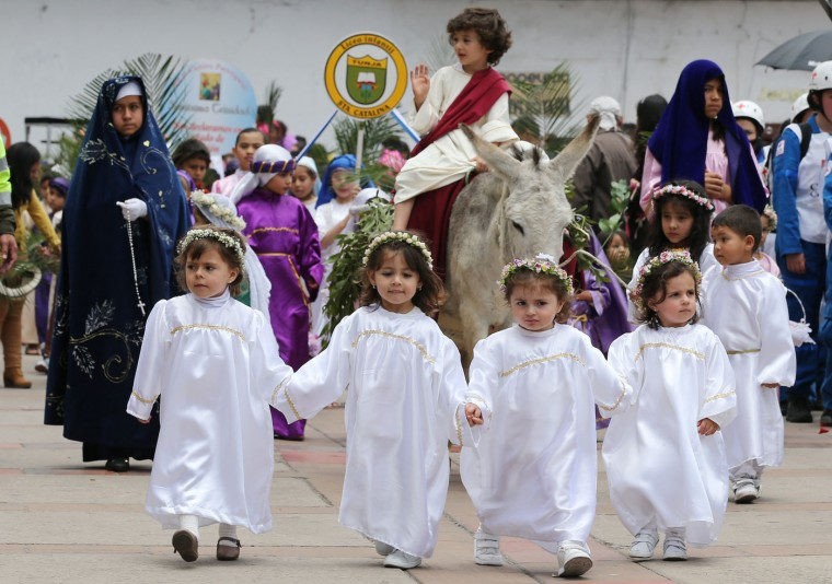 Children dressed as angels lead a boy portraying Jesus Christ and his triumphant return to Jerusalem, in the Children's Holy Thursday Procession, in Tunja, Colombia, Thursday, April 2, 2015. In this annual Holy Week tradition, now in its 55th year, children carry religious floats, and depict the key moments of the passion, death and resurrection of Jesus Christ. (AP Photo/Fernando Vergara)