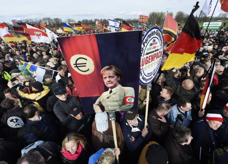 Demonstrators hold a poster depicting German Chancellor Angela Merkel in a jacket that resembles Third Reich uniforms with a Euro sign on the sleeve at a rally called 'Patriotic Europeans against the Islamization of the West' (PEGIDA) in Dresden, Germany, Monday, April 13, 2015. (AP Photo/Jens Meyer)