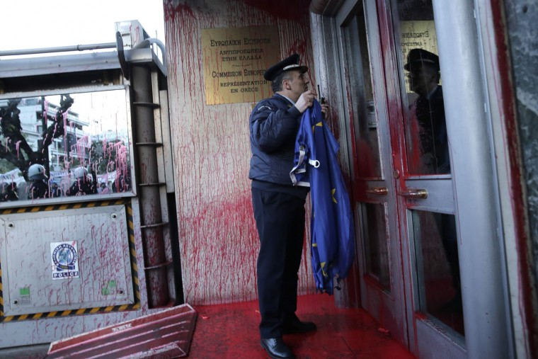 A police officer holds an EU flag outside the paint-spattered entrance of the European Commission office, during a march to protest migrant deaths in the Mediterranean in central Athens, on Thursday, April 23, 2015. European Union leaders on Thursday started committing new resources to save lives in the Mediterranean at an emergency summit convened after hundreds of migrants drowned in the space of a few days, and were discussing laying the ground for military action against traffickers.(AP Photo/Petros Giannakouris)