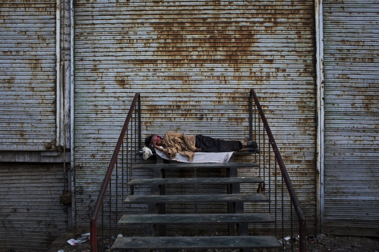 A homeless man sleeps outside shops with their shutter down New Delhi, India, Thursday, April 16, 2015. The International Monetary Fund (IMF) and the World Bank have forecast India's growth to rise up to 7.5 per cent next fiscal, overtaking China as the fastest growing emerging economy in 2015-16. (AP Photo/Bernat Armangue)