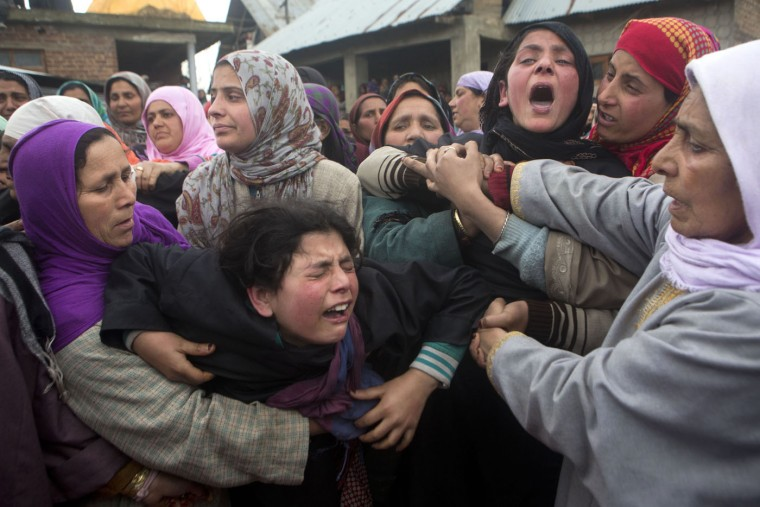 Unidentified women try to comfort Asmat Shafi, center in black, and Sakeena Shafi, third right in black, during the funeral procession of their father Mohammad Shafi, an Indian policeman killed in a gunbattle, in Chenabal, some 21 Kilometers north of Srinagar, Indian controlled Kashmir, Thursday, April 2, 2015. Suspected Kashmiri rebels and Indian security personnel were engaged in a fierce gunbattle Thursday after government forces intercepted two suspected militants taking shelter in the village in the Indian-controlled portion of Kashmir, police officer K. Rajendran said. (AP Photo/Dar Yasin)