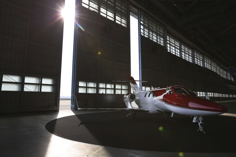 A HondaJet is displayed at the venue of a press conference at a hangar at Tokyo's Haneda airport Thursday, April 23, 2015. Honda, known for making motorcycles and cars, is showing its new sleek business jet in Japan for the first time, billing it as quiet, quick and green. The jet, on show at the airport on Thursday, is the culmination of founder Soichiro Honda's longtime dream to have a plane in Honda Motor Co.'s lineup. (AP Photo/Eugene Hoshiko)