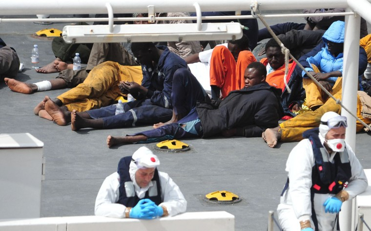Survivors of the smuggler's boat that overturned off the coasts of Libya lie on the deck of the Italian Coast Guard ship Bruno Gregoretti, in Valletta's Grand Harbour, Monday, April 20 2015. A smuggler's boat crammed with hundreds of people overturned off Libya's coast on Saturday as rescuers approached, causing what could be the Mediterranean's deadliest known migrant tragedy and intensifying pressure on the European Union Sunday to finally meet demands for decisive action. So far rescuers saved 28 people a recovered 24 bodies. (AP Photo/Lino Azzopardi)
