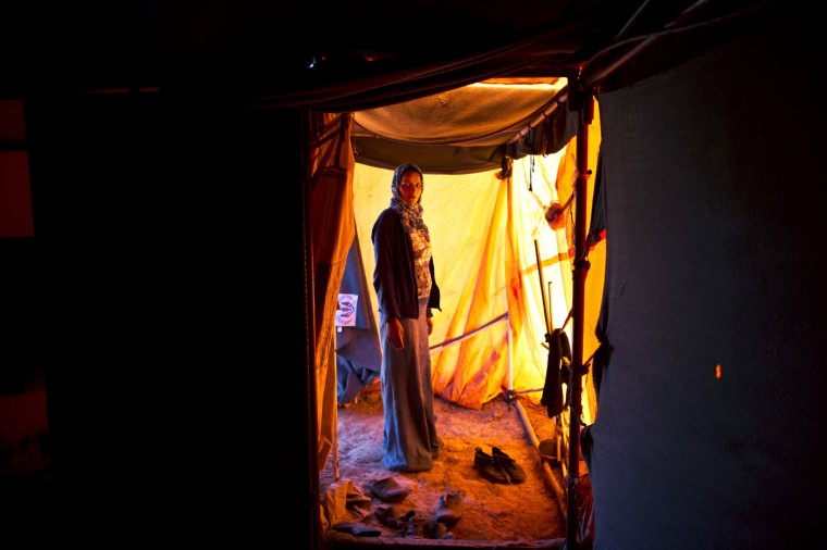 In this Monday, March 16, 2015 photo, Syrian refugee Feedah Ali, 18, who is four months pregnant, poses for a portrait inside her tent at an informal settlement near the Syrian border, on the outskirts of Mafraq, Jordan. Pregnant refugee women living in these settlements are among the most vulnerable of the hundreds of thousands of Syrians who have found shelter in Jordan. By contrast, pregnant women in Jordan's three recognized refugee camps have access to free services, including pre-natal care and delivery, according to the U.N. refugee agency. (AP Photo/Muhammed Muheisen)