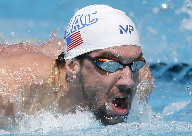 Michael Phelps competes in the men's 100 meter butterfly preliminary, Thursday, April 16, 2015, at the Arena Pro Swim Series in Mesa, Ariz. The race was the 18-time Olympic champions first competition after serving a six-month suspension for DUI. (AP Photo/Matt York)