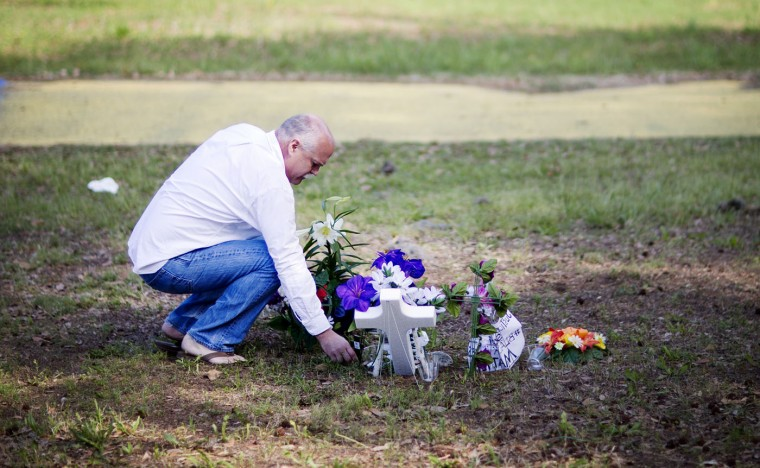 "Jeffrey Spell, of Charleston, S.C., places flowers at the scene where Walter Scott was killed by a North Charleston police officer Saturday, after a traffic stop in North Charleston, S.C., Thursday, April 9, 2015. ""I've worked in North Charleston for many years and I'm troubled by the whole thing. I thought it would be respectable,"" said Spell about why he brought the flowers. ""Nationwide, the cops are killing people. There has to be other ways of making arrests,"" Spell said. The officer, Michael Thomas Slager, has been fired and charged with murder. (AP Photo/David Goldman)"