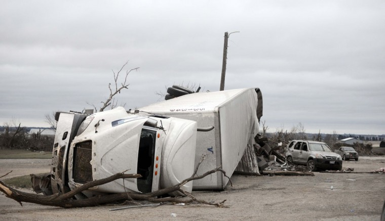 A rolled over semi-trailer sits among debris at Route 64 and 251 in Rochelle, Ill., Friday, April 10, 2015, after a tornado past through the area Thursday evening. The National Weather Service says at least two tornadoes churned through six north-central Illinois counties Thursday night. One person was killed in the small town of Fairdale, Ill. (AP Photo/Daily Herald, Paul Michna)