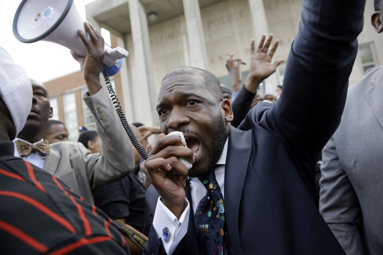 The Rev. Jamal Bryant leads a rally outside of the Baltimore Police Department's Western District police station during a march and vigil for Freddie Gray, Tuesday, April 21, 2015, in Baltimore. Gray died from spinal injuries a week after he was arrested and transported in a police van. (AP Photo/Patrick Semansky)