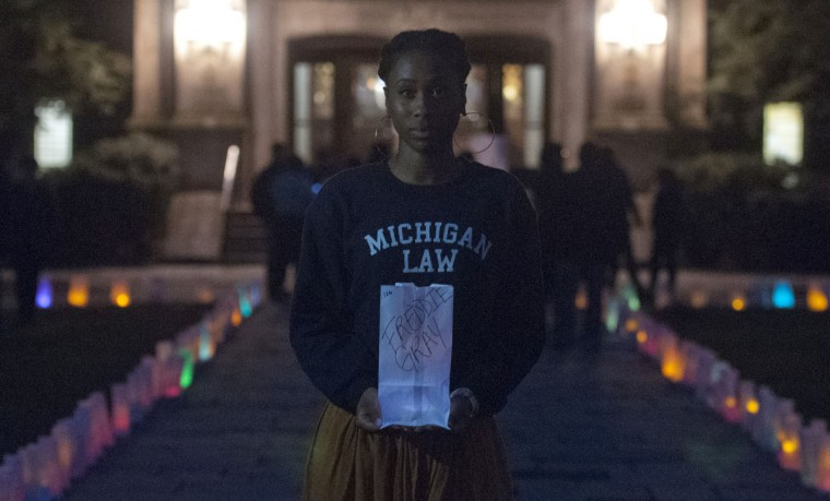 Kya Henley, President of Racial Justice Coalition, stands for a photo while holding a bag displaying the name of Freddie Gray, who died while in police custody, during the Luminary Candlelight Vigil on the Law Quad Thursday, April 30 2015, in Ann Arbor, Mich. (Nicole Hester/The Ann Arbor News via AP)