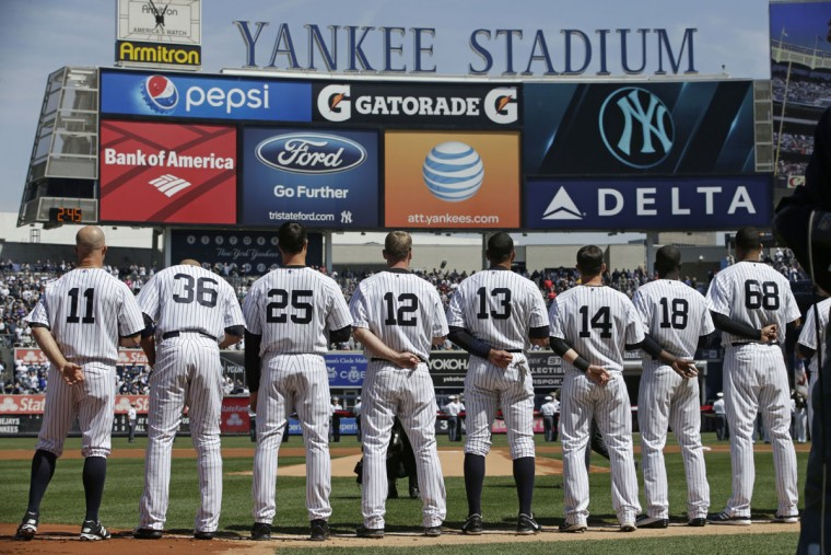 Members of the New York Yankees line up on the baseline for player introductions and during the singing of the National Anthem in an opening day baseball game against the Toronto Blue Jays in New York, Monday, April 6, 2015. (AP Photo/Kathy Willens)