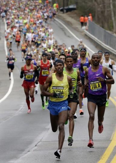 Lelisa Desisa, of Ethiopia, leads the pack through Hopkinton, Mass., en route to a win in the Boston Marathon, Monday, April 20, 2015, in Boston. (AP Photo/Steven Senne)