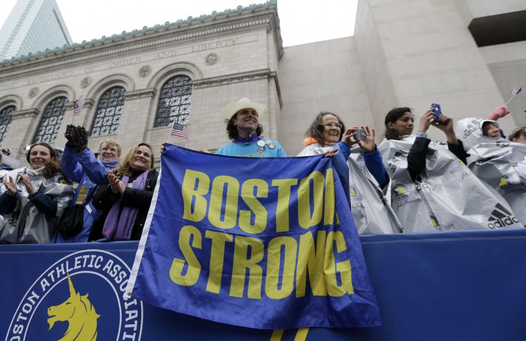"Carlos Arredondo, a 2013 Boston Marathon first-responder, holds a ""Boston Strong"" banner beside his wife Melida, right, in the grandstand near the Boston Marathon finish line Monday, April 20, 2015 in Boston. (AP Photo/Elise Amendola)"