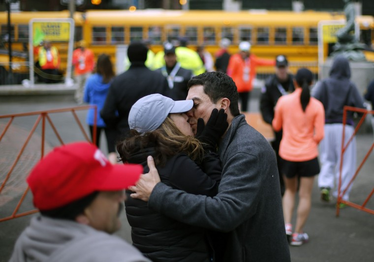 Boston Marathon runner Richard Flores, of Phoenix, gets a kiss from his wife, Tina, before boarding a shuttle bus in Boston to the starting line in Hopkinton, Mass., Monday, April 20, 2015. (AP Photo/Robert F. Bukaty)