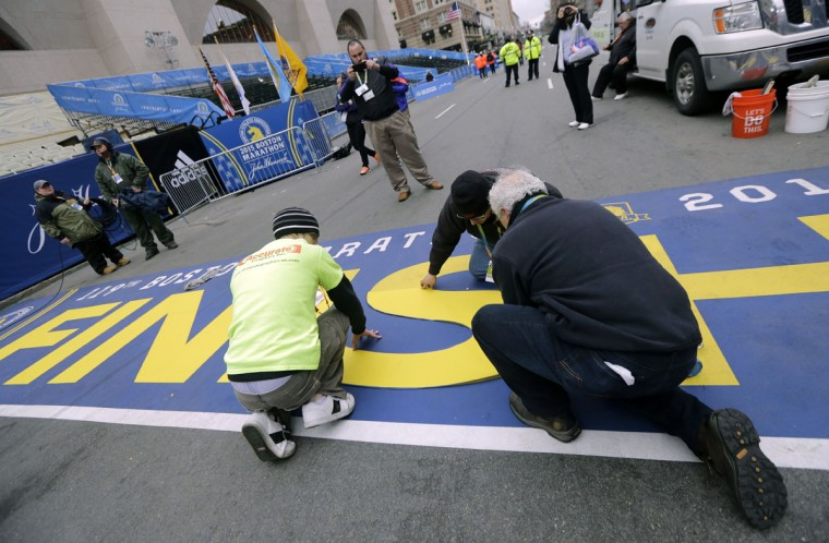 Workers touch up the finish line before the start of the Boston Marathon Monday, April 20, 2015 in Hopkinton, Mass. (AP Photo/Elise Amendola)