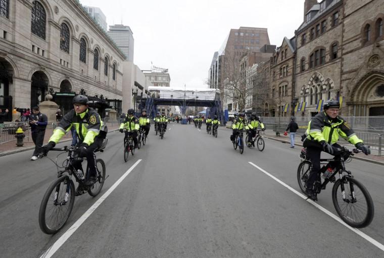 Police officers patrol near the finish line of the Boston Marathon, Monday, April 20, 2015, in Boston. (AP Photo/Elise Amendola)
