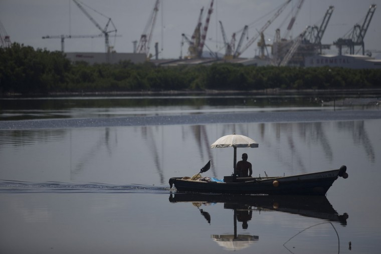 In this March 3, 2015 photo, a fisherman returns to the dock in the Vila Pinheiro slum, part of the Mare complex in Rio de Janeiro, Brazil. For decades, fishermen have trolled the bay that will host Olympic sailing events in 2016, hoping to catch sea bass, Atlantic bigeyes and shrimp. But slowly, year after year, the catches have diminished. The men blame industrial and sewage pollution for their empty nets. (AP Photo/Leo Correa)