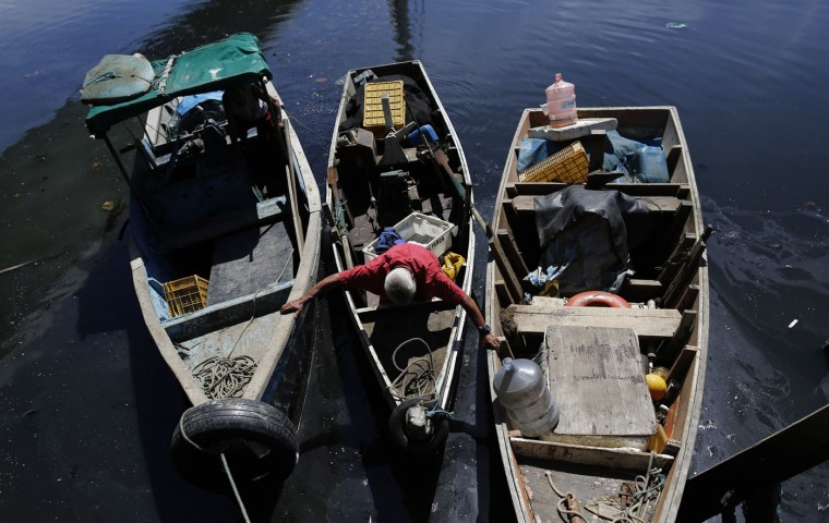 """In this March 3, 2015 photo, fisherman Cicero Romao Batista docks his boat at the dock in the Vila Pinheiro slum, part of the Mare complex in Rio de Janeiro, Brazil. Batista said that getting in and out of the dock is a """"sacrifice"""" due to the trash littering the bay. The 69-year-old widow said he's been fishing since the 1970's and sometimes sleeps on his boat. (AP Photo/Leo Correa)"""