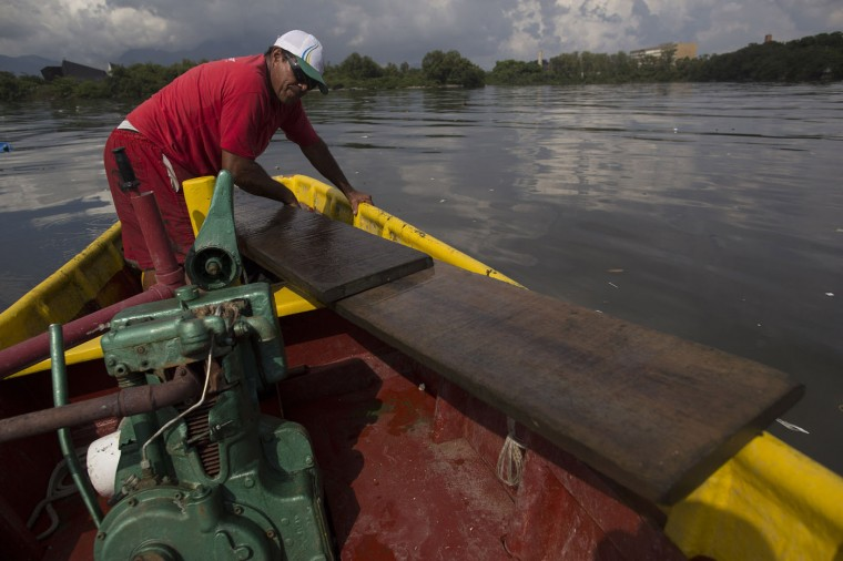 In this Feb. 28, 2015 photo, fisherman Edmo Rodrigues da Costa, 59, pulls planks of wood into his boat which he found floating in Guanabara bay as he made his way back to the docks after a morning of fishing in Rio de Janeiro, Brazil. A good day two decades ago would bring in $200 worth of fish, but today, Costa says a successful haul fetches $50. Sometimes the floating trash he finds is worth more than his catch, like these two large planks of hardwood. (AP Photo/Leo Correa)