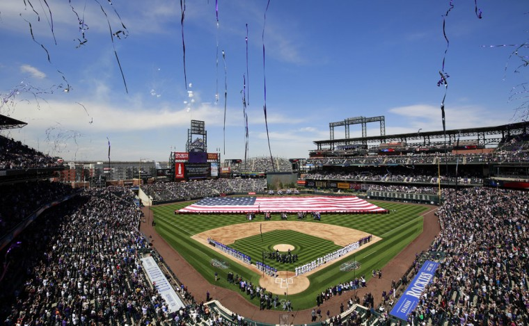 Streamers fly following the singing of the national anthem on Opening Day for the Colorado Rockies vs. the Chicago Cubs, Friday, April 10, 2015, in Denver. (AP Photo/Jack Dempsey)