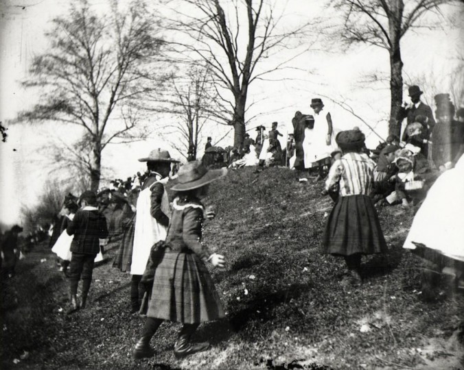 "This 1889 photo released by the National Archives shows children egg hunting in Washington. In 1889, eleven years after the Easter Egg Roll became a White House tradition, President Benjamin Harrison added music: The United States Marine Band, also known as ""The President's Own,"" played as children romped on the South Lawn. (AP Photo/Library of Congress, Francis Benjamin Johnston)"