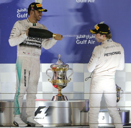 Mercedes driver Lewis Hamilton of Britain, left, and Mercedes driver Nico Rosberg of Germany spray rose water on each other after Hamilton wins the Bahrain Formula One Grand Prix at the Formula One Bahrain International Circuit in Sakhir, Bahrain, Sunday, April 19, 2015. Ferrari driver Kimi Raikkonen of Finland. (AP Photo/Kamran Jebreili)