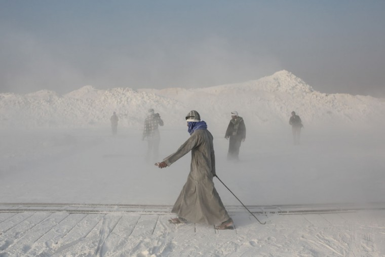 Limestone quarry workers walk through a cloud of dust spewed into the air by rotor blades of the stone-cutting machinery in the desert of Minya, southern Egypt. (AP Photo/Mosa'ab Elshamy)