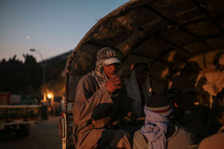 A quarry worker keeps warm after dawn by drinking tea as he and others are transported in pick-up trucks to work in Minya, southern Egypt. The quarries are the main employers in the province, some 300 kilometers (180 miles) south of Cairo. (AP Photo/Mosa'ab Elshamy)