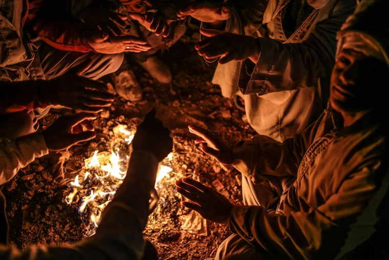 Quarry workers try to keep themselves warm around a bonfire as they wait for work after dawn in Shurafa village, Minya, southern Egypt. (AP Photo/Mosa'ab Elshamy)