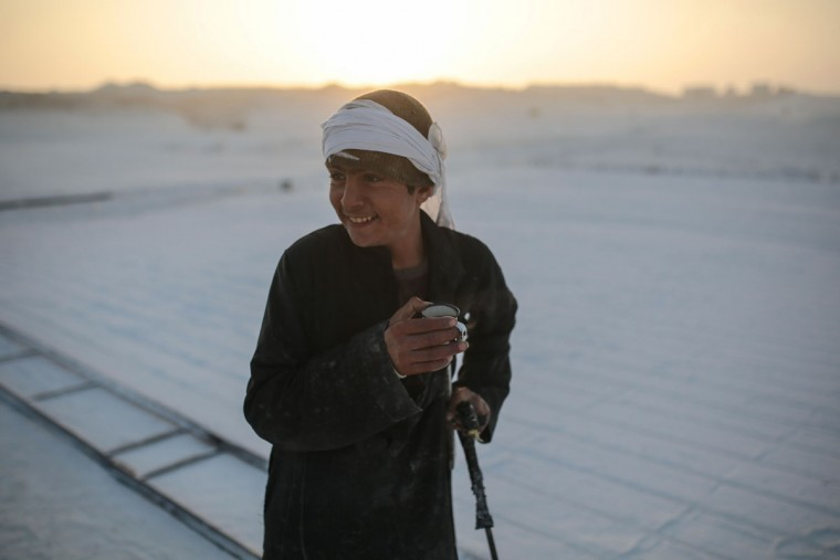 A young worker smiles during a tea break at sunrise in the desert of Minya, southern Egypt. Some children as young as 10 years old work in the quarries to help their families, risking injury and sometimes death. (AP Photo/Mosa'ab Elshamy)