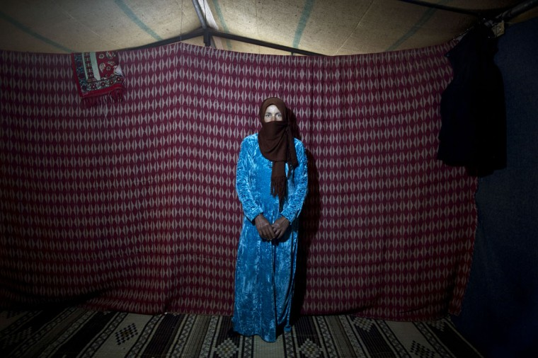 In this Monday, March 16, 2015 photo, Syrian refugee Thuraya Nayif, 40, a mother of seven children in her second month of pregnancy, poses for a photograph inside her tent at an informal settlement near the Syrian border, on the outskirts of Mafraq, Jordan. Pregnant refugee women living in informal tent settlements are among the most vulnerable of the hundreds of thousands of Syrians who have found shelter in Jordan. They often can't afford doctor visits and face potential health hazards because of lack of running water and other challenges. (AP Photo/Muhammed Muheisen)