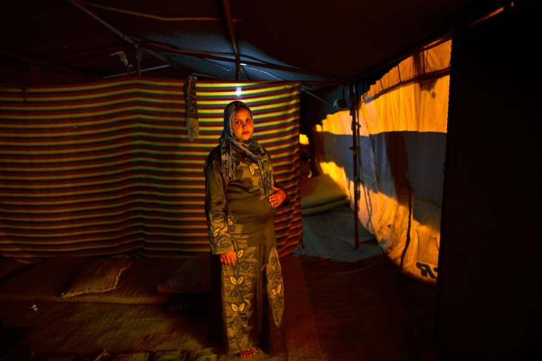 In this Monday, March 16, 2015 photo, pregnant Syrian refugee Bushra Eidah, 15, poses for a portrait during her ninth month inside her tent at an informal settlement near the Syrian border, on the outskirts of Mafraq, Jordan. Pregnant refugee women living in informal tent settlements are among the most vulnerable of the hundreds of thousands of Syrians who have found shelter in Jordan. They often canít afford doctor visits and face potential health hazards because of lack of running water and other challenges. (AP Photo/Muhammed Muheisen)