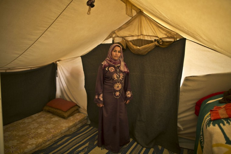 In this Monday, March 16, 2015 photo, Syrian refugee Khalida Moussa, 28, a mother of three children who is six months pregnant, poses for a picture inside her tent at an informal tented settlement near the Syrian border, on the outskirts of Mafraq, Jordan. (AP Photo/Muhammed Muheisen)