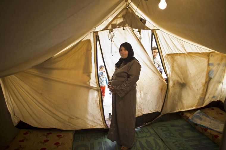 In this Monday, March 16, 2015 photo, Syrian refugee Taleea Farhan, 33, a mother of four children who is seven months pregnant, poses for a photograph inside her tent at an informal tented settlement near the Syrian border, on the outskirts of Mafraq, Jordan. (AP Photo/Muhammed Muheisen)