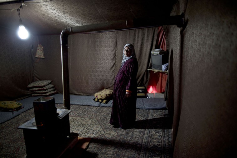 In this Tuesday, March 17, 2015 photo, Syrian refugee Mahdiya Alkhalid, 36, poses for a portrait at nine months pregnant inside her tent at an informal settlement near the Syrian border, on the outskirts of Mafraq, Jordan. Unlike expectant mothers in informal tented settlements, pregnant women in Jordanís three recognized refugee camps have access to free services, including pre-natal care and delivery, according to the U.N. refugee agency. Zaatari, the largest camp, saw more than 3,500 births last year, out of a total more than 18,000 babies born to refugee mothers in 2014, the agency says. (AP Photo/Muhammed Muheisen)