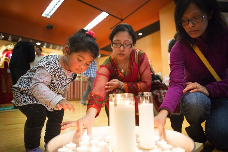 Samataa Shrestha, 21 months, helps her mom Pragya, center, place a small candle onto a plate as friend Beenu Maharjan does the same during a community gathering and prayer organized by the Nepal Seattle Society at the Hindu Temple and Cultural Center in Bothell, Wash. on Sunday, April 26, 2015. Shrestha and Maharjan are both from Nepal, and say their family members are safe. (Lindsey Wasson/The Seattle Times via AP)